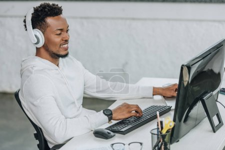 Photo for Happy african american programmer sitting at workplace in headphones - Royalty Free Image