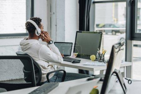 Photo pour Mise au point sélective du programmeur américain africain assis au lieu de travail dans les écouteurs - image libre de droit
