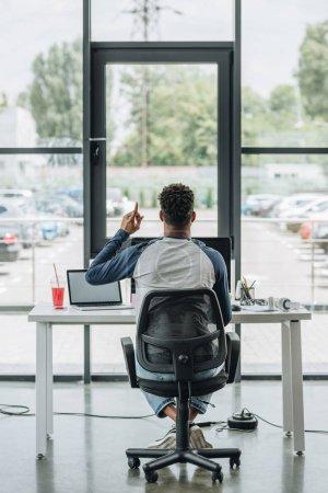 Photo pour Vue arrière du jeune programmeur afro-américain montrant signe d'idée tout en étant assis sur le lieu de travail dans le bureau - image libre de droit