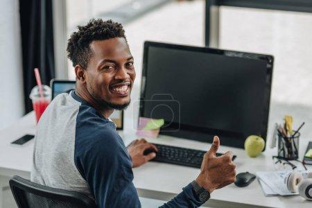 Photo pour Programmeur afro-américain joyeux regardant la caméra et montrant pouce vers le haut tout en étant assis près des ordinateurs - image libre de droit