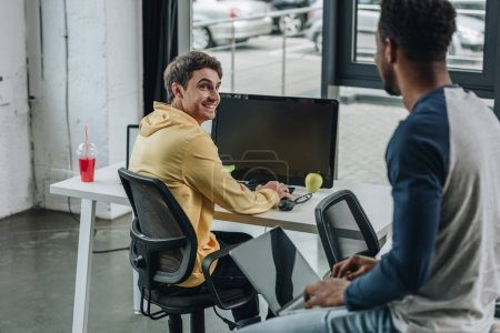 cheerful programmer looking at african american colleague sitting on desk in office