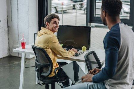 fröhlicher Programmierer mit Blick auf einen afrikanisch-amerikanischen Kollegen, der im Büro am Schreibtisch sitzt
