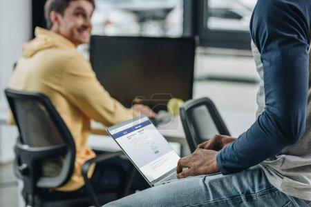 Photo pour KYIV, UKRAINE - 29 JUILLET 2019 : vue recadrée d'un programmeur afro-américain utilisant un ordinateur portable avec le site Facebook à l'écran près d'un collègue souriant - image libre de droit