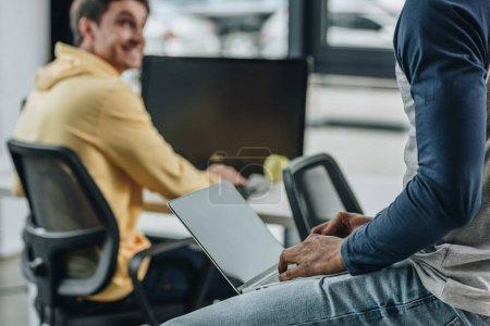 Photo pour Vue partielle du programmeur afro-américain assis sur le bureau avec ordinateur portable près d'un collègue souriant - image libre de droit