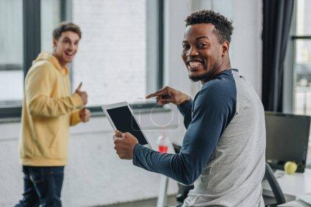 Photo pour Souriant programmeur afro-américain pointant avec le doigt à la tablette numérique proche collègue montrant pouce vers le haut - image libre de droit