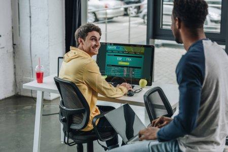 Photo pour KYIV, UKRAINE - 29 JUILLET 2019 : programmeur souriant utilisant un ordinateur avec le site Web Sportsbet à l'écran tandis que son collègue afro-américain assis sur le bureau avec un ordinateur portable - image libre de droit