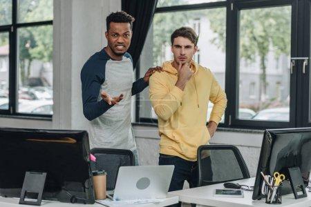 Photo pour Programmeur afro-américain irrité gesticulant alors qu'il se tenait près de son collègue au bureau - image libre de droit