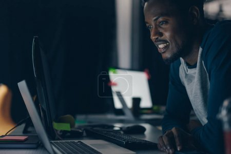 Photo for Young african american programmer smiling while looking at computer monitor at night in office - Royalty Free Image