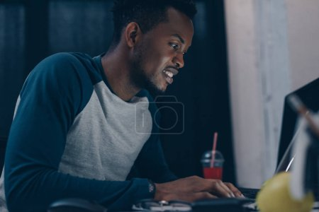 Photo for Smiling african american programmer sitting at workplace at night - Royalty Free Image