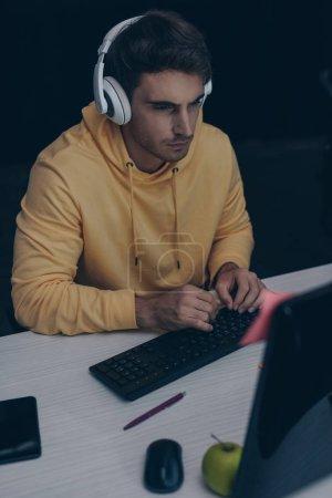 Photo pour Jeune programmeur dans les écouteurs travaillant la nuit au bureau - image libre de droit