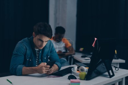 Photo for Selective focus of young programmer using smartphone while sitting near african american colleague at night in office - Royalty Free Image