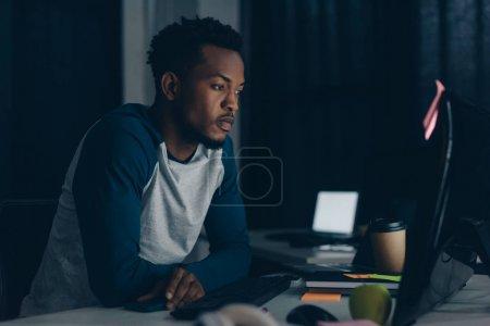 Photo pour Programmeur afro-américain réfléchi travaillant la nuit au bureau - image libre de droit