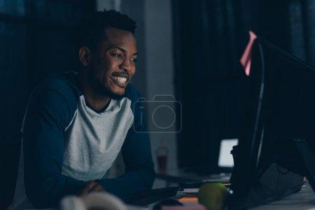 Photo pour Joyeux programmeur afro-américain souriant tout en regardant le moniteur d'ordinateur - image libre de droit