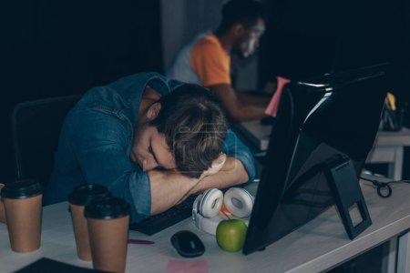 Photo pour Foyer sélectif de programmeur fatigué dormant sur le lieu de travail près d'un collègue afro-américain - image libre de droit