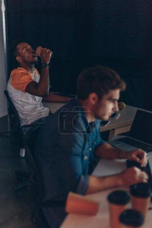 Photo pour Foyer sélectif du programmeur afro-américain boire du café à emporter tout en travaillant près de collègue multiculturel la nuit au bureau - image libre de droit