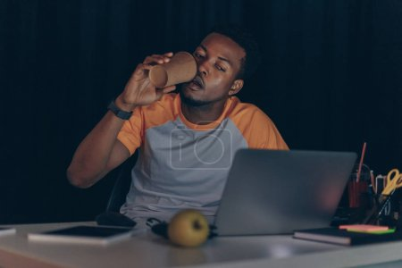 Photo for Young african american programmer drinking coffee to go while working at night in office - Royalty Free Image