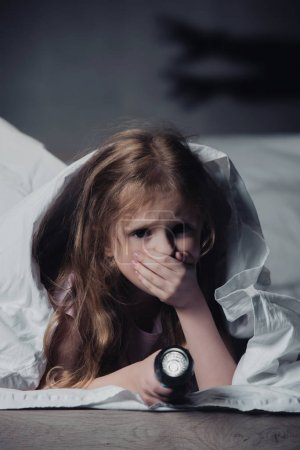 Photo for Scared child holding flashlight while hiding under blanket on black background with shadows - Royalty Free Image
