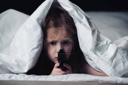 Photo for Frightened child holding gun and looking at camera while hiding under blanket isolated on black - Royalty Free Image