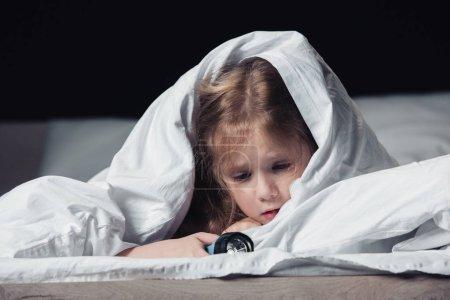 Photo for Scared child holding flashlight while hiding under white blanket isolated on black - Royalty Free Image