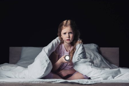 Photo for Scared kid sitting under blanket, holding flashlight and looking at camera isolated on black - Royalty Free Image