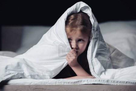Photo for Frightened child hiding under blanket and looking away isolated on black - Royalty Free Image