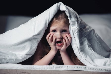 Photo for Scared kid screaming and holding hands on face while hiding under blanket isolated on black - Royalty Free Image