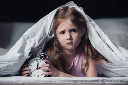 Photo for Frightened kid lying under blanket with alarm clock and looking at camera isolated on black - Royalty Free Image