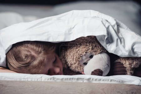 Photo for Frightened child lying under blanket near teddy bear isolated on black - Royalty Free Image