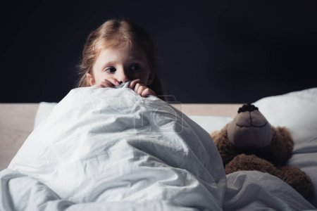 Photo for Scared kid looking away while sitting under blanket near teddy bear isolated on black - Royalty Free Image