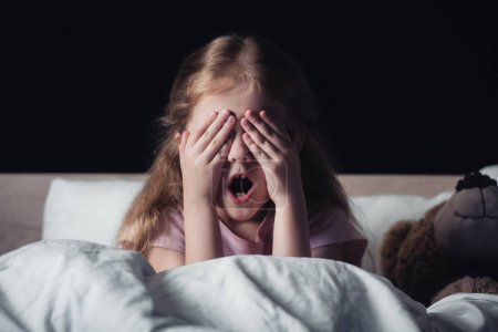 Photo for Frightened kid screaming and covering eyes with hands while sitting on bedding near teddy bear isolated on black - Royalty Free Image
