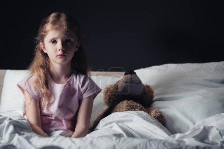 Photo pour Enfant effrayé assis sur la literie près de l'ours en peluche et regardant la caméra isolée sur noir - image libre de droit