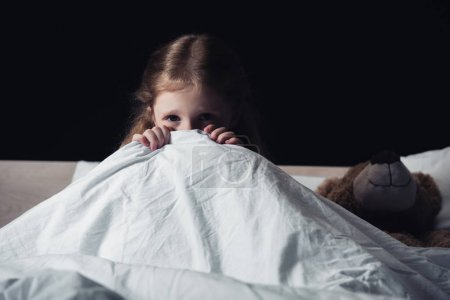 Photo for Scared child hiding under blanket while sitting on bedding near teddy bear isolated on black - Royalty Free Image