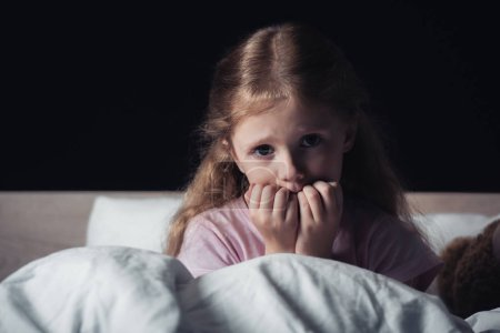 Photo for Scared child looking at camera while sitting on bedding isolated on black - Royalty Free Image