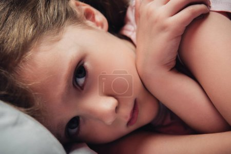 Photo for Cute, frightened child looking at camera while lying in dark bedroom - Royalty Free Image