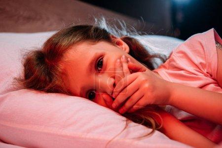 Photo pour Enfant effrayé regardant l'appareil-photo tout en se trouvant dans le lit et affichant le signe de silence - image libre de droit