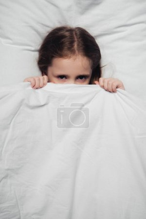 Photo for Top view of scared child hiding under blanket and looking at camera - Royalty Free Image