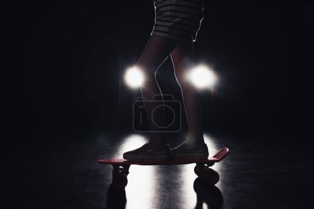 Photo for Cropped view of kid riding penny board in darkness with illumination of headlights on black background - Royalty Free Image