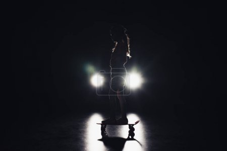 Photo for Child riding penny board in darkness with illumination of headlights on black background - Royalty Free Image