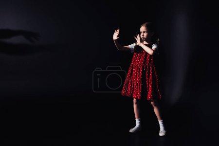 Photo pour Enfant effrayé restant dans l'obscurité avec les mains tendues sur le fond noir - image libre de droit