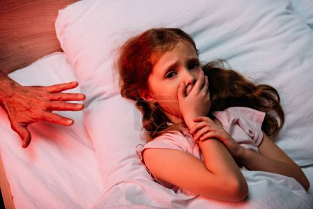 male hand near scared child showing hush sign and looking at camera while lying in bed