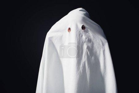 Photo pour Horrible fantôme dans drap de lit blanc isolé sur noir - image libre de droit