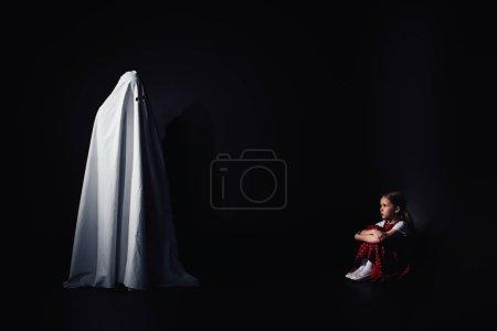 Photo pour Enfant effrayé assis sur le sol et regardant fantôme blanc terrible sur fond noir - image libre de droit