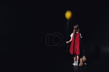 Photo for Back view of depressed child with yellow balloon and teddy bear isolated on black - Royalty Free Image