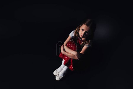 Photo for Sad, scared child sitting on floor and looking at camera on black background - Royalty Free Image