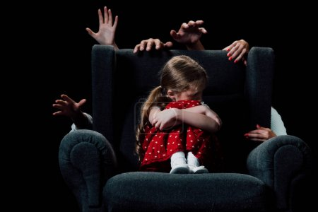 Photo for Scared child sitting in armchair surrounded with human hands isolated on black - Royalty Free Image