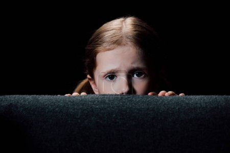 Photo for Scared child hiding behind armchair and looking at camera isolated on black - Royalty Free Image