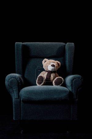 Photo pour Fauteuil doux gris avec ours en peluche de nounours d'isolement sur le noir - image libre de droit