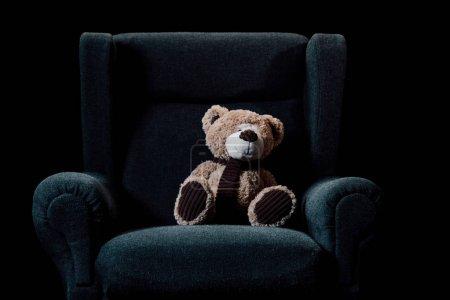 Photo pour Ours en peluche beige dans le fauteuil doux gris d'isolement sur le noir - image libre de droit