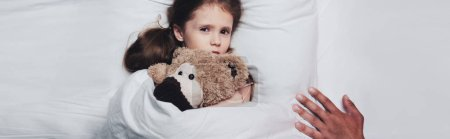 Photo for Partial view of male hand near scared child lying in bed with teddy bear, panoramic shot - Royalty Free Image