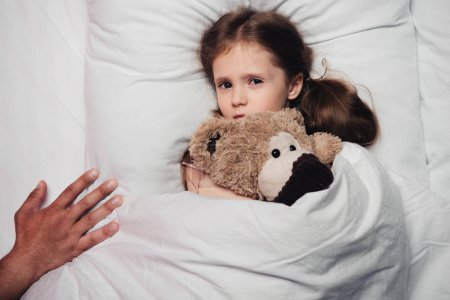 Photo for Cropped view of male hand near scared child lying in bed with teddy bear - Royalty Free Image